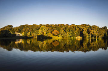 The sun rises over the changing colourful Autumn leaves at Stourhead, Wiltshire.
