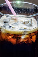 Glass of cola drink with ice and straw