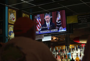 Bar patrons watch as President Barack Obama addresses the nation from the Oval Office on December 6, 2015 at the DFW Airport in Irving, Texas.