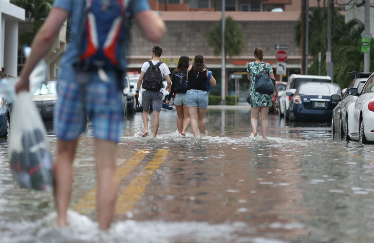 MIAMI BEACH, FL - SEPTEMBER 29: People walk through a flooded street that was caused by the combination of the lunar orbit which caused seasonal high tides and what many believe is the rising sea levels due to climate change on September 29, 2015 in Miami Beach, Florida. The City of Miami Beach is in the middle of a five-year, $400 million storm water pump program and other projects that city officials hope will keep the ocean waters from inundating the city as the oceans rise even more in the future. (Photo by Joe Raedle/Getty Images)