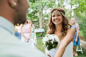 Bride with bouquet smiling at groom backyard wedding