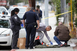 Investigators work a crime scene around a white Acura vehicle after the arrest of a man found with assault weapons and possible explosives, who told authorities he was in town for the city's gay pride parade in Santa Monica, California, U.S., June 12, 2016.