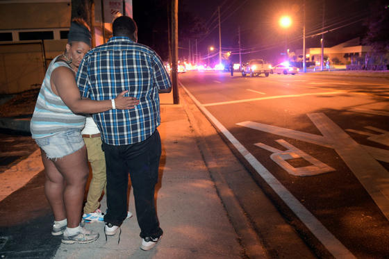Bystanders wait down the street from a multiple shooting at the Pulse nightclub in Orlando, Fla., Sunday, June 12, 2016. A gunman opened fire at a nightclub in central Florida, and multiple people have been wounded, police said Sunday.