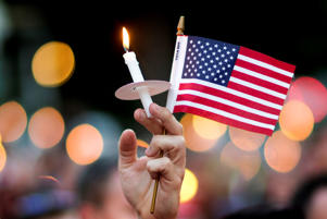 A mourner holds up an American flag and a candle during a vigil for a fatal shooting at an Orlando nightclub, Sunday, June 12, 2016, in Atlanta.