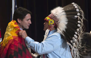 AFN National Chief Perry Bellegarde adjusts a blanket presented to Prime Minister Justin Trudeau following speeches at the Assembly of First Nations Special Chiefs Assembly in Gatineau, Tuesday Dec. 8, 2015.