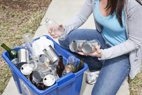 Woman putting cans and bottles in recycling bin.