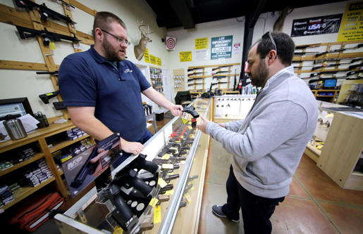 Mike Howse, left, helps David Foley as he shops for a handgun at the Spring Guns...