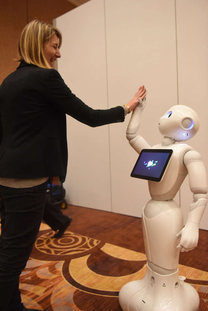 Pepper, a humanoid robot by Aldebaran Robotics and SoftBank Mobile, high-fives with Aurore Chiquot, in the media room during CES Press Day, January 5, 2016 in Las Vegas, Nevada ahead of the CES 2016 Consumer Electronics Show. Pepper is a social robot created to converse, recognize and react to emotions. AFP PHOTO / ROBYN BECK / AFP / ROBYN BECK (Photo credit should read ROBYN BECK/AFP/Getty Images)
