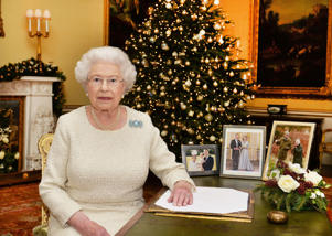 Queen Elizabeth II sits at a desk in the 18th Century Room at Buckingham Palace, London.