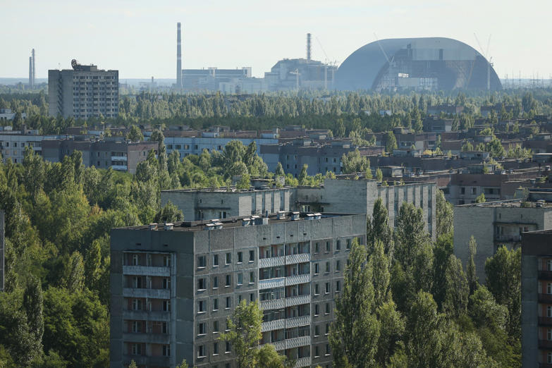 The former Chernobyl nuclear power plant, including destroyed reactor four (C), as well as the New Safe Confinement structure (R) that will one day enclose the remains of reactor four, stand behind the abandoned city of Pripyat on September 30, 2015 near Pripyat, Ukraine.
