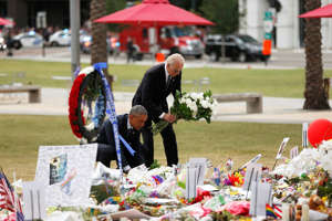 President Barack Obama and Vice President Joe Biden place flowers at a memorial in Orlando, Fla., June 16, in honor of people killed in the shooting at a gay nightclub.