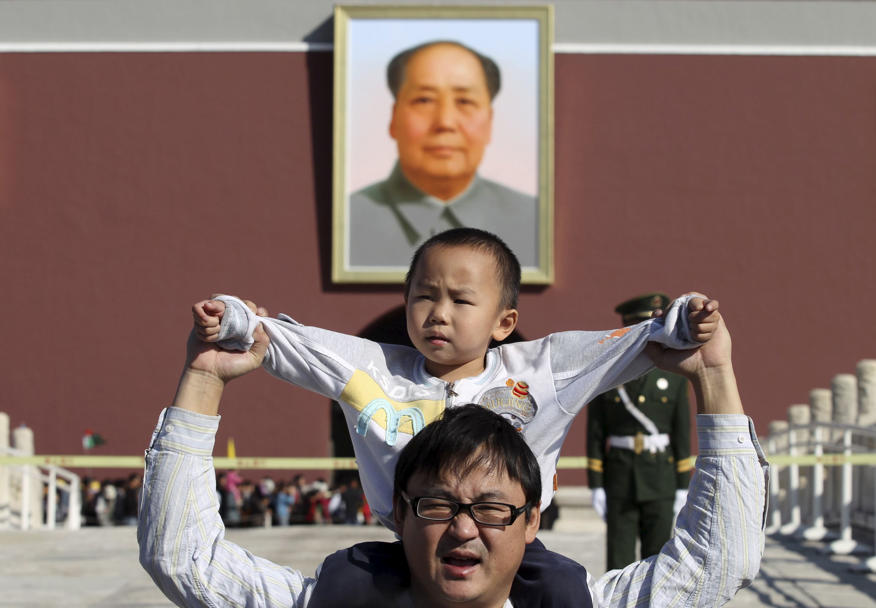 A boy sits on his father's shoulders as they pose for a photograph in front of the giant portrait of late Chinese chairman Mao Zedong on the Tiananmen Gate, in Beijing.<br />