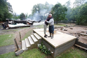 Jimmy Scott gets a hug from Anna May Watson, left, as they clean up from severe ...
