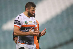 James Tedesco of the Tigers receives attention from the trainer during the round 13 NRL match.