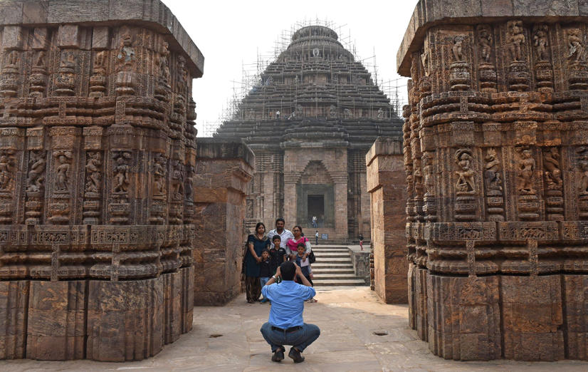 Tourists visits the Konark Sun temple in Konark, in eastern Orissa state on December 12, 2014. The Konark Sun Temple is a 13th-century Sun Temple built by King Narasimhadeva I of the Eastern Ganga Dynasty around 1250. The temple, a UNESCO World Heritage Site, has been built in the shape of a gigantic chariot with elaborately carved stone wheels, pillars and walls and a major part of the structure is now in ruins.