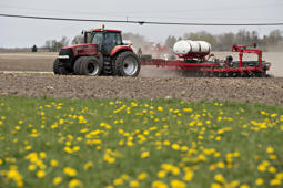 A Case IH tractor pulls a planter through a field as corn is planted in Princeton, Illinois, U.S., on Monday, April 18, 2016. The U.S. Department of Agriculture (USDA) is scheduled to release a monthly report on farm prices on April 29. Photographer: Daniel Acker/Bloomberg