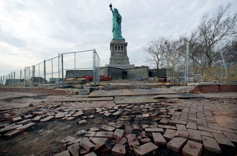 In this Nov. 30, 2012 file photo, the Statue of Liberty stands beyond parts of a brick walkway damaged in Superstorm Sandy on Liberty Island in New York. With scientists forecasting sea levels to rise by anywhere from several inches to several feet by 2100, historic structures and coastal heritage sites around the world are under threat. A multidisciplinary conference is scheduled to convene in Newport, R.I., this week to discuss preserving those structures and neighborhoods that could be threatened by rising seas.