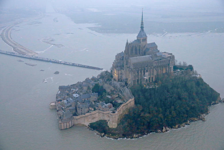 "An aerial view shows the Mont Saint-Michel off France's Normandy coast March 20, 2015. The Mont Saint-Michel 11th century abbey is expected to be entirely surrounded by the English Channel following exceptionally high spring tides. Parts of the French coast will be on alert for the so-called ""tide of the century"", with tidal coefficients of 118 and 119 respectively on March 20 and 21."