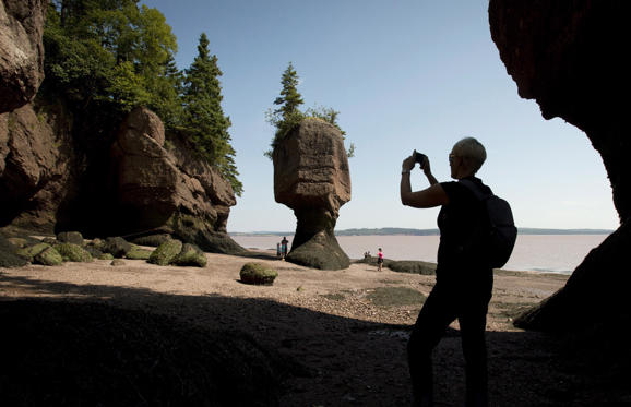 Slide 1 of 10: A tourist stops to take a photo of the Hopewell Rocks on the Bay of Fundy, N.B., Friday, August, 16, 2013.