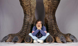 American director Steven Spielberg poses between a pair of giant dinosaur feet in a publicity still for the film 'Jurassic Park', 1993.  (Photo by Murray Close/Getty Images)