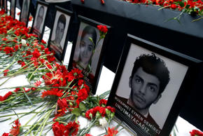 Photographs of victims were displayed among carnations as family members, collea...