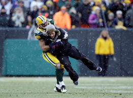 Green Bay Packers' Brad Jones tackles a fan that ran on the field during the sec...