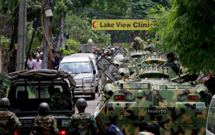 Bangladeshi soldiers come out of an area housing a restaurant popular with forei...