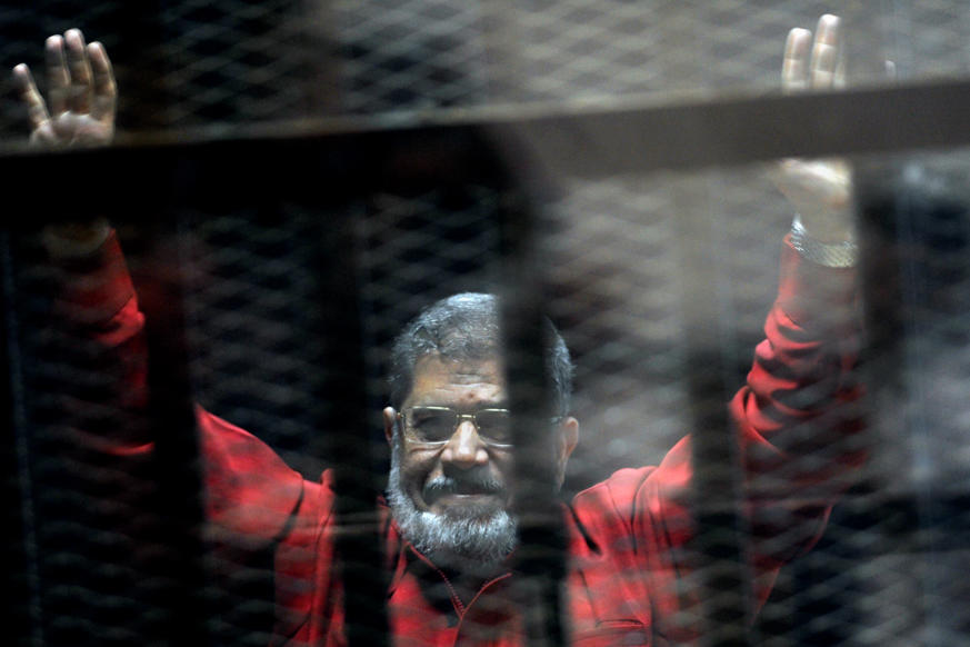 FILE - In this June 21, 2015 file photo, former Egyptian President Mohammed Morsi, wearing a red jumpsuit that designates he has been sentenced to death, raises his hands inside a defendants cage in a makeshift courtroom at the national police academy, in an eastern suburb of Cairo, Egypt.