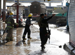 Afghan fire-fighters and members of security forces clean the site of a suicide attack in Kabul, Afghanistan June 20, 2016.
