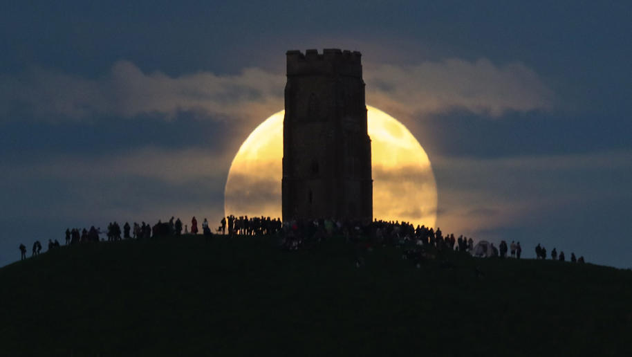 GLASTONBURY, ENGLAND - JUNE 20:  A full moon rises behind Glastonbury Tor as people gather to celebrate the summer solstice on June 20, 2016 in Somerset, England. Tonight's strawberry moon, a name given to the full moon in June by Native Americans becaus