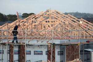 A construction worker labors on a house under construction in the suburb of Pukekohe in Auckland, New Zealand