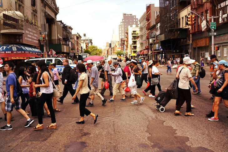 In this file photo, people walk through New York's Chinatown district on July 11, 2014 in New York City.