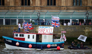 A boat decorated with flags and banners from the 'Fishing for Leave' group that is campaigning for a 'leave' vote in the E.U. referendum sails by the British Houses of Parliament as part of a