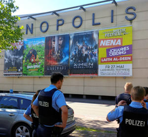 German police walks past a cinema complex after a masked man with a gun and ammunition belt opened fire in Viernheim