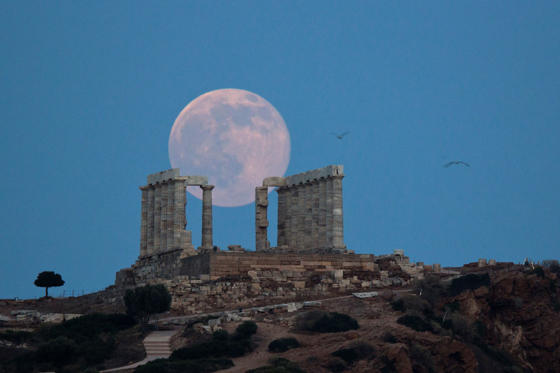 Seagulls fly as the full moon rises behind the ancient marble Temple of Poseidon at Cape Sounion, southeast of Athens, on the eve of the summer solstice on June 20, 2016. The temple located on a promontory at Cape Sounion, about 70 Km (45 miles) south-so