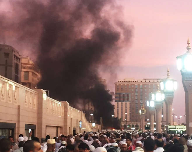 In this photo provided by Noor Punasiya, people stand by an explosion site in Medina, Saudi Arabia, Monday, July 4, 2016. State-linked Saudi news websites reported an explosion Monday near one of Islam's holiest sites in the city of Medina, as two suicid