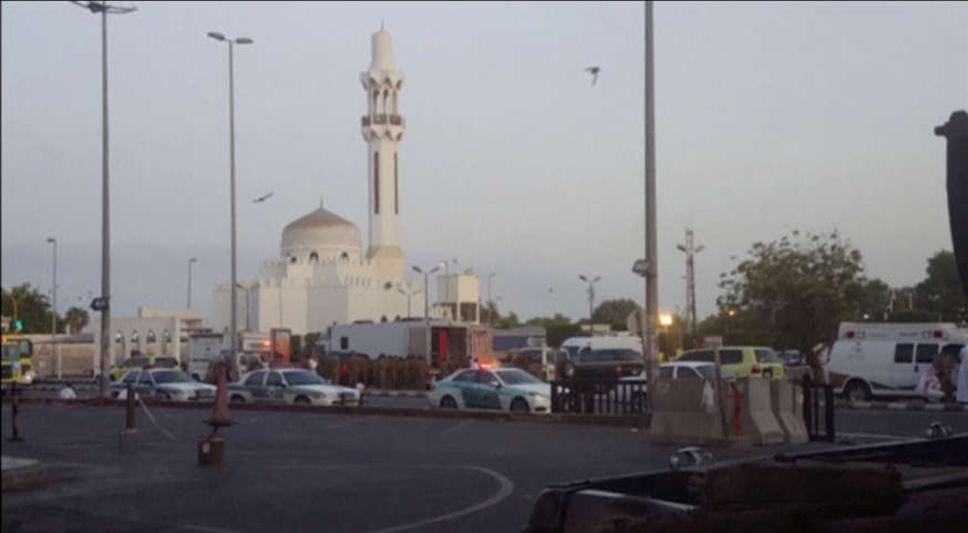 General view of security personnel in front of a mosque as police stage a second controlled explosion, after a suicide bomber was killed and two other people wounded in a blast near the U.S. consulate in Jeddah, Saudi Arabia, in this still frame taken fr