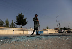 An Afghan policeman stands guard after an attack at the American University of A...