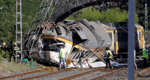 Rescue workers inspect a train that derailed in Galicia in north-western Spain, close to the town of O Porrino on Sept. 9.