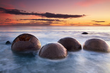 The Moeraki Boulders are unusually large and spherical boulders lying along a stretch of Koekohe Beach on the Otago coast of New Zealand. Christopher Chan