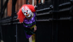 "POSED BY MODEL A person wearing a clown costume in a street in Liverpool. The ""killer clown"" craze has continued to spread across the UK"