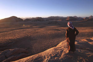 WADI RUM, JORDAN - MARCH 28:  Abu Sultan a Bedouin guide looks over the desert of Wadi Rum at sunset on March 28, 2013 in Wadi Rum, Jordan.  (Photo by Adam Pretty/Getty Images)