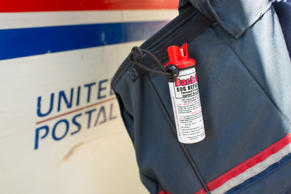 A can of dog repellent hangs from a bag of a United States Postal Service (USPS)...
