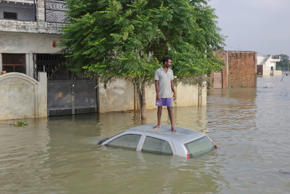 An Indian man, stands on his car that got submerged in flood waters as he waits for a boat next to his house in Allahabad, Uttar Pradesh state, India, Saturday, Aug. 27, 2016. Flood water levels stabilized with rains ebbing over the past four days in this northern state, where 200,000 people had moved to relief centers after their homes were submerged