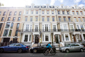 A cyclist passes a row of residential homes on Vicarage Gate in London