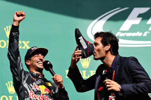 Mark Webber drinks champagne from the boot of Daniel Ricciardo.