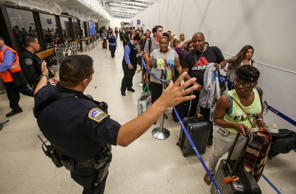 Police officers stand guard as passengers wait in line at Terminal 7 in Los Ange...