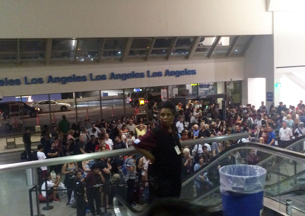 A crowd of people wait in Terminal 1 where passengers were being rescreened by security at Los Angeles International Airport after reports that a gunman opened fire Sunday, Aug. 28, 2016.