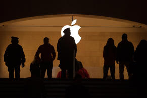 A police officer is silhouetted against the Apple logo in Grand Central Terminal in the Manhattan borough of New York