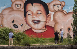 People stand in front of a new graffiti by artists Justus Becker and Oguz Sen depicting Alan Kurdi.